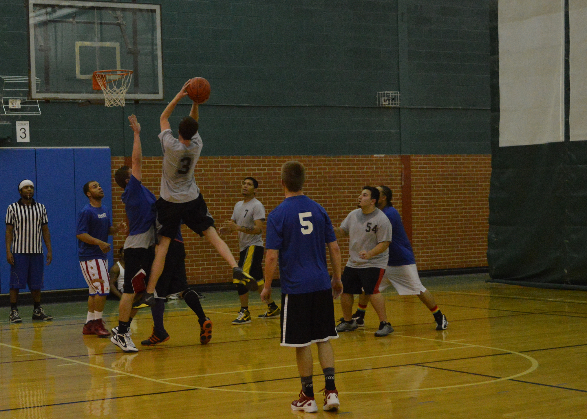 Photo by EDUARDO OLMOS | Team Dashit (blue) vs. Team Free Agents (grey). General studies major Jeremy Briscoe, #3 of Free Agents, attempts the shot at the Washington St Campus, Carter Fitness Center.