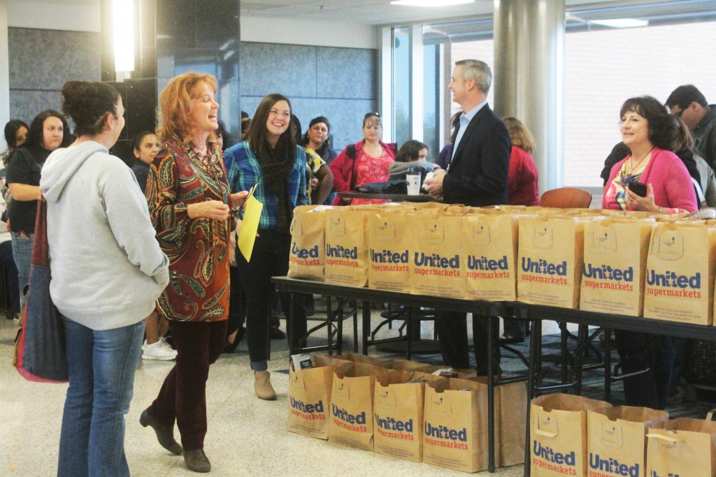 Lynae Jacob discusses this year's Thanksgiving bags from the AC Food Pantry in the Parcells-Byrd lobby Nov. 20 as KAMR-TV anchors Jackie Kingston and Andy Justus prepare to hand them out.