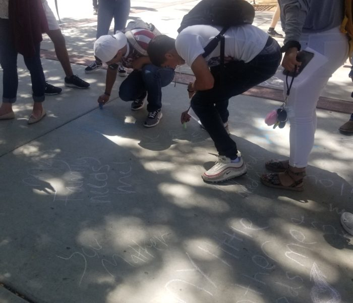 people writing on the sidewalk